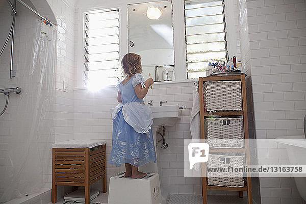 Weibliches Kleinkind steht auf Stufe Zähne putzen