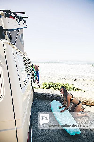 Frau beim Wachsen eines Surfbretts neben einem Wohnmobil