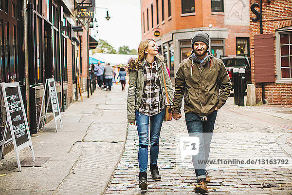 Young couple strolling on cobbled street,  Boston,  Massachusetts,  USA
