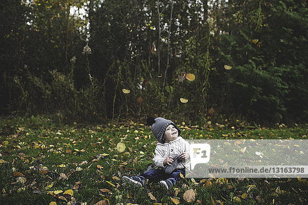 Baby boy wearing bobble hat sitting on grass watching falling autumn leaves smiling