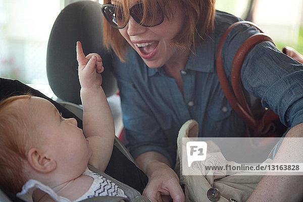 Mutter setzt Baby-Tochter in Autositz