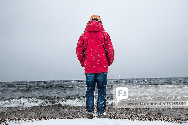 Rückansicht eines jungen Mannes in rotem Mantel in voller Länge mit Blick auf den Ozean