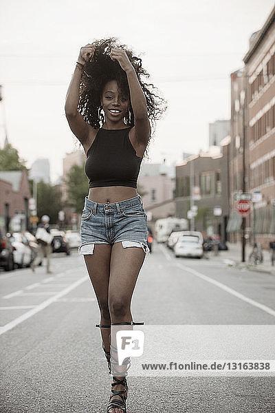 Junge Frau steht auf der Straße mit Händen in den Haaren