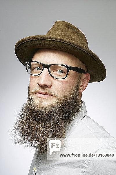 Studioporträt eines mittleren erwachsenen Mannes in Trilby mit übergroßem Bart