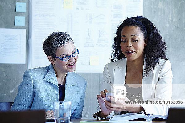 Zwei durch Smartphone abgelenkte Geschäftsfrauen