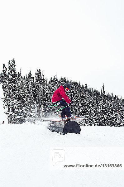 Seitenansicht eines Skifahrers beim Schleifen auf einem röhrenförmigen Hindernis  Whistler Terrain Park  British Columbia  Kanada