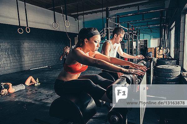 Menschen  die an Übungsgeräten im Fitnessstudio trainieren