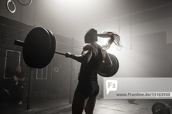 Young woman lifting barbell in gym  rear view