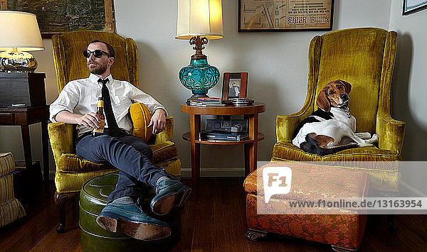 Junger Mann und Haushund entspannen sich im Sessel im Wohnzimmer