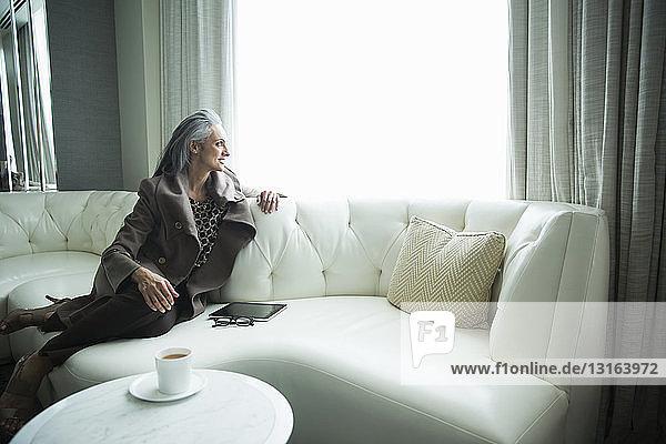 Porträt einer reifen Frau auf weißem Luxussofa liegend