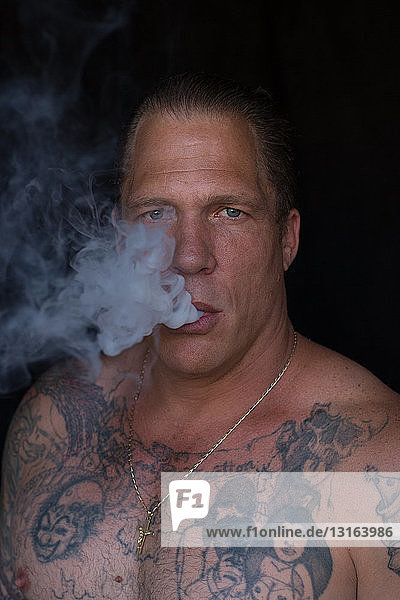 Portrait of bare chested tattooed mature man  hair slicked back looking at camera blowing smoke