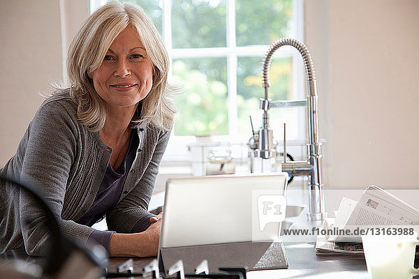 Frau benutzt Tablet-Computer in der Küche