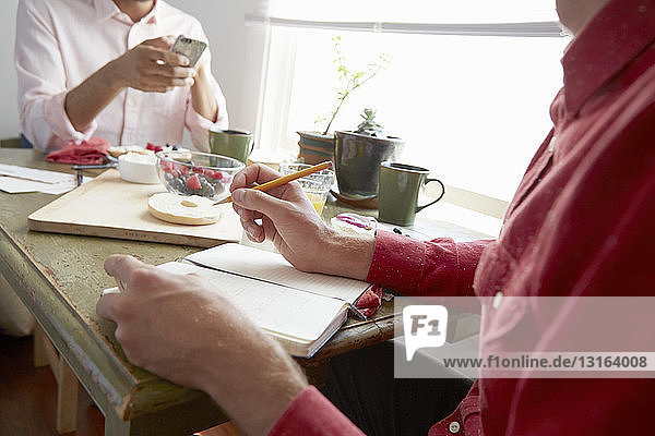 Cropped view of men sitting at dining table drinking orange juice looking at smartphone  writing in notebook
