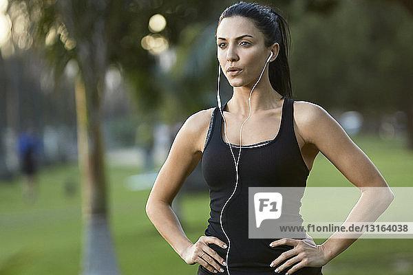 Mid adult woman wearing earphones  hands on hips