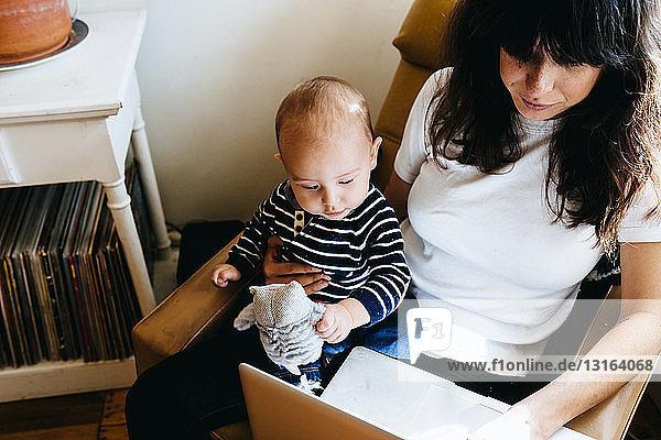 Mother using laptop with son on lap