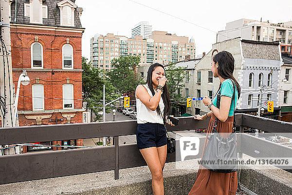 Junge Frauen stehen auf dem Balkon