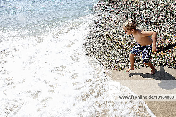 Boy playing on beach  Laguna Beach  California  US