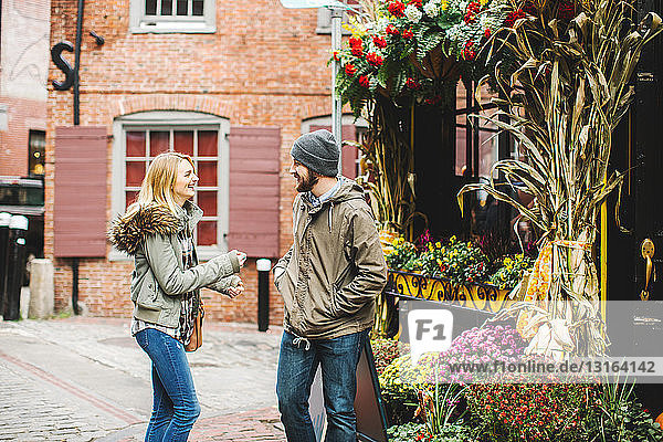 Young couple chatting on cobbled street outside florists  Boston  Massachusetts  USA