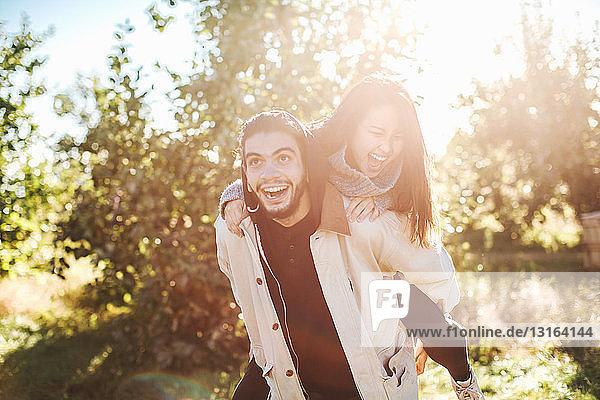 Junger Mann nimmt junge Frau Huckepack,  im Freien