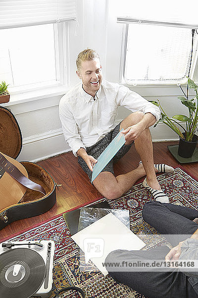 Man sitting in bay window holding record looking at friend smiling