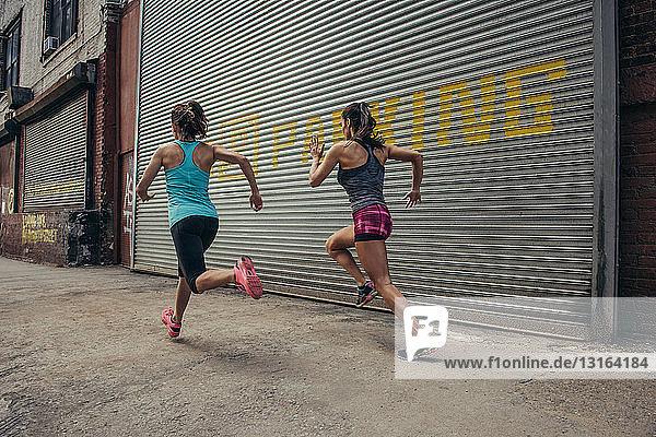 Zwei Läuferinnen laufen auf der Straße in der Stadt