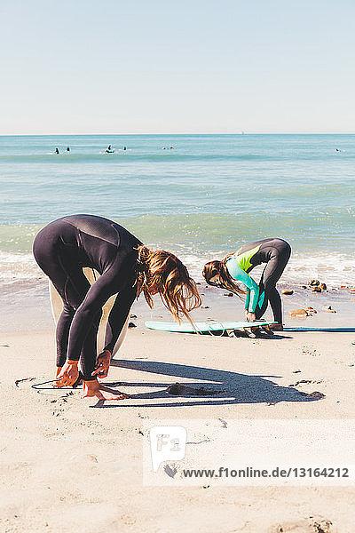 Paar am Strand  Surfbretter an den Knöcheln befestigen