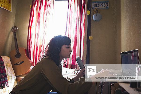 Junge Frau benutzt Laptop mit Mikrofon