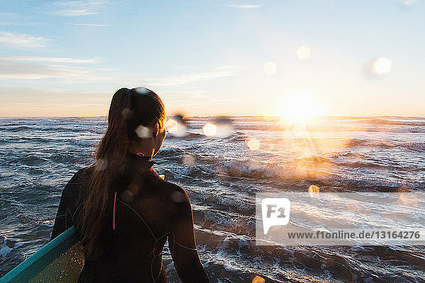 Rear view of female surfer wading into sea at sunset  Cardiff-By-The-Sea  California  USA