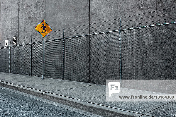 Crosswalk sign  wire fence and wall