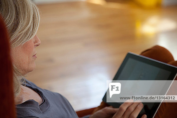 Reife Frau mit digitalem Tablett