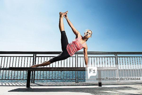 Frau praktiziert Yoga auf Parkbank