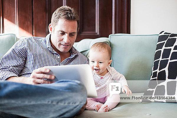 Vater benutzt Tablette mit Baby-Tochter