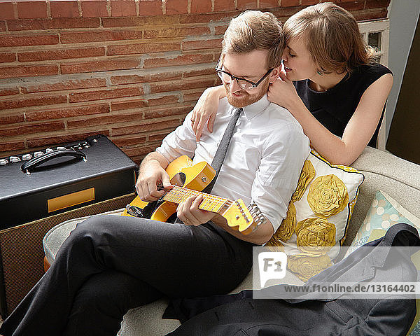 Young woman with partner practising on electric guitar