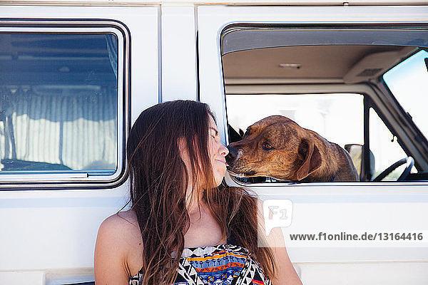 Haushund im Wohnwagen  streckt die Hand aus  um das Gesicht der Frau neben dem Wagen zu lecken