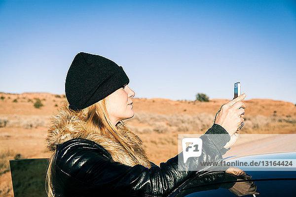 Frau fotografiert neben dem Auto  Kayenta  Arizona  USA