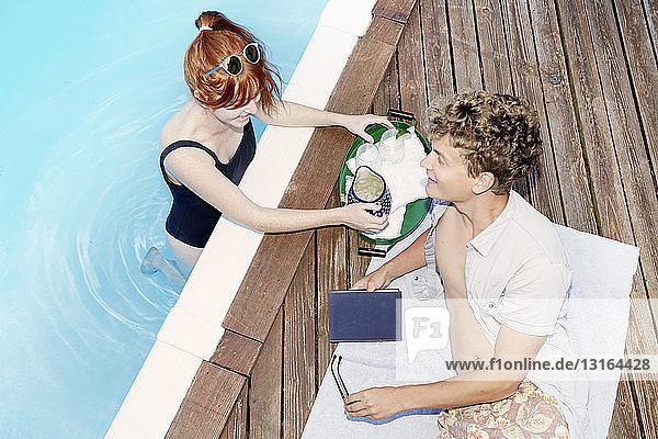 Draufsicht auf ein junges Paar  das sich am Pool unterhält