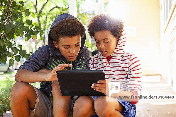 Zwei Brüder benutzen Touchscreen auf digitalem Tablet im Garten
