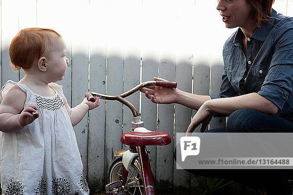 Mutter hilft Baby-Tochter mit Dreirad