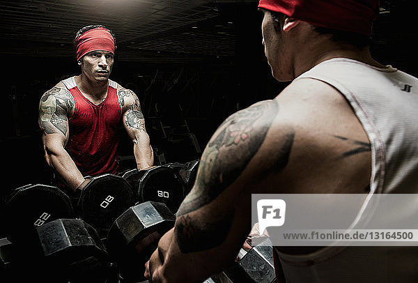 Muskulöser junger Mann schaut in den Sportspiegel