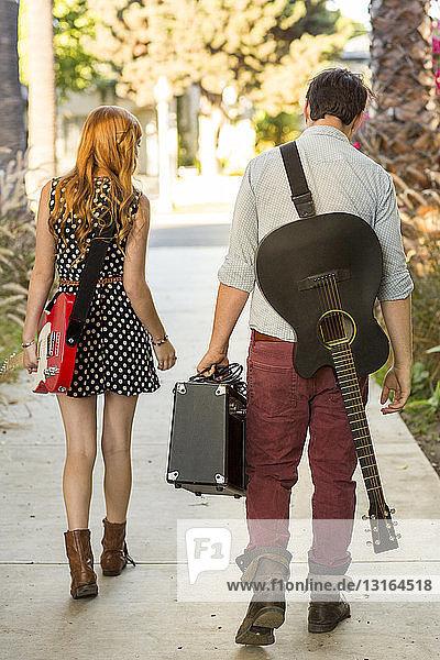 Junges Paar geht mit Gitarren und Verstärker die Straße entlang