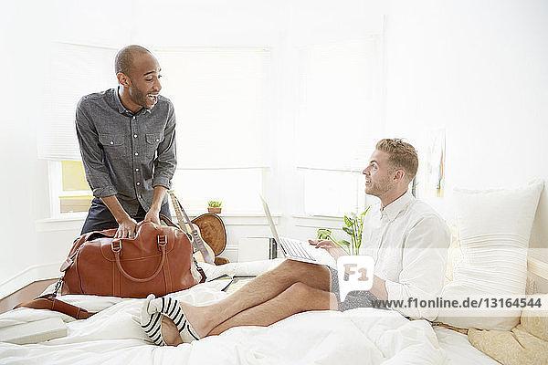 Homosexuelles Paar packt Reisetasche und benutzt Laptop-Computer im Bett