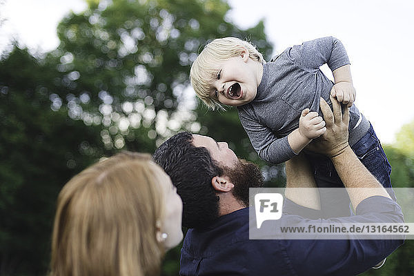 Mother and father playing with son  outdoors