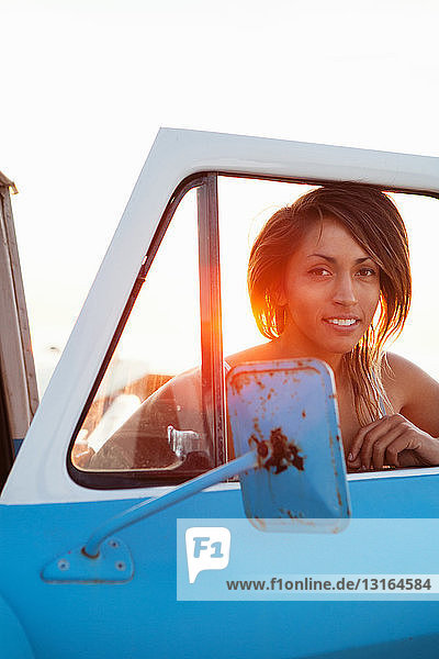 Portrait of young female surfer through pick up truck window  Leucadia  California  USA