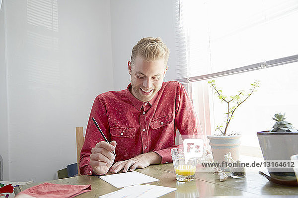 Man sitting at dining table looking down writing letter smiling