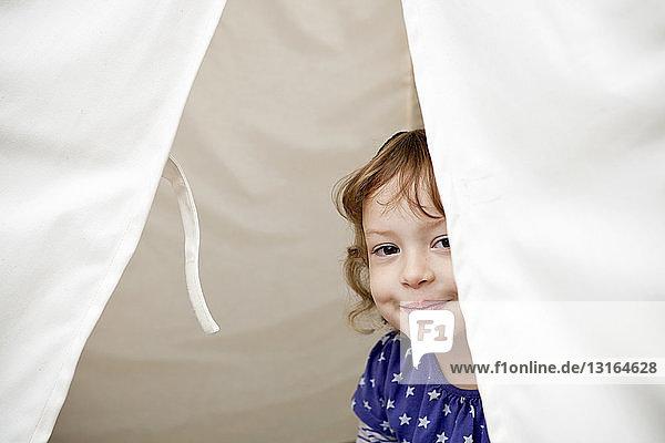 Porträt eines weiblichen Kleinkindes  das aus dem Zelt schaut