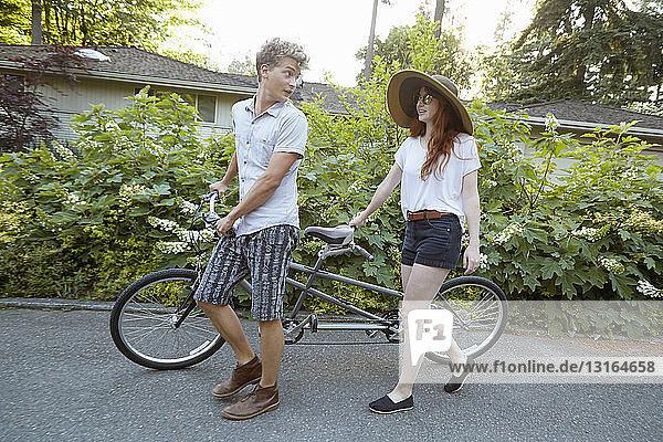 Junges Paar auf Vorstadtstraße bereitet sich auf Tandemfahrt vor