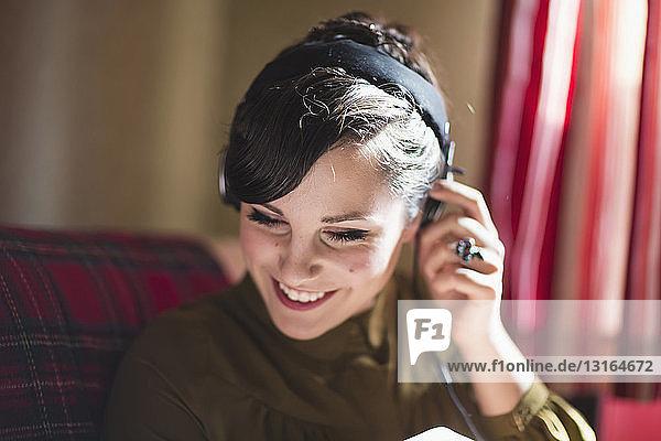 Junge Frau sitzt auf dem Sofa und hört Musik über Kopfhörer