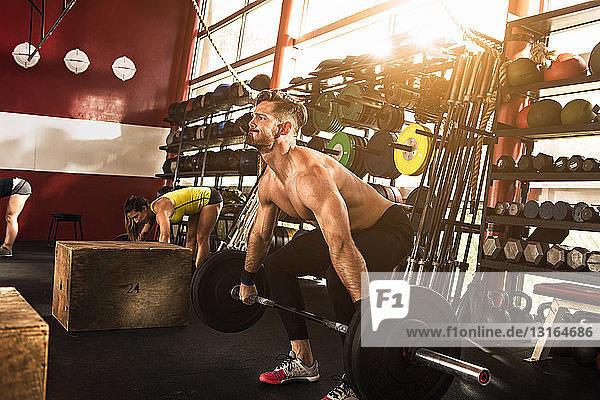 Bodybuilder beugt sich zum Heben einer Langhantel im Fitnessstudio
