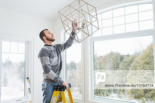 Young man installing ceiling light