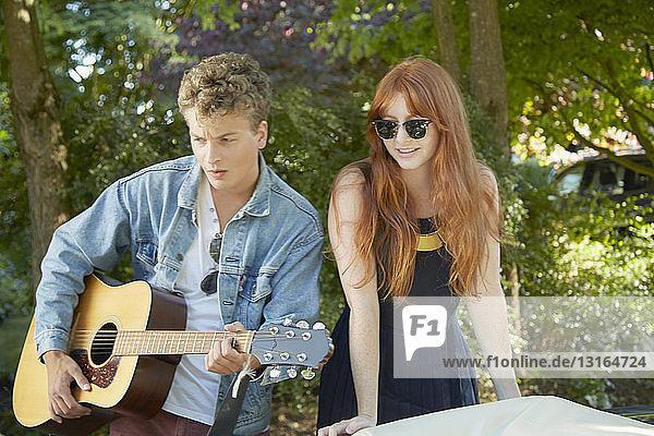 Junges Paar spielt akustische Gitarre